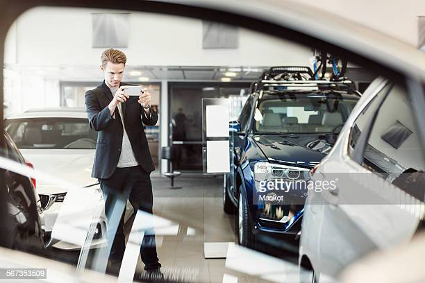 Man photographing car through mobile phone at dealership store
