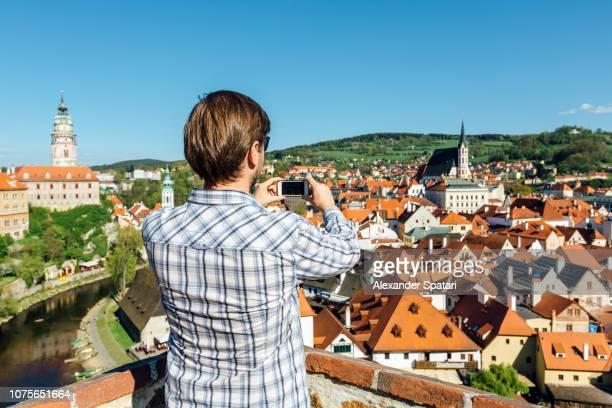 Man photographing Cesky Krumlov skyline with smartphone