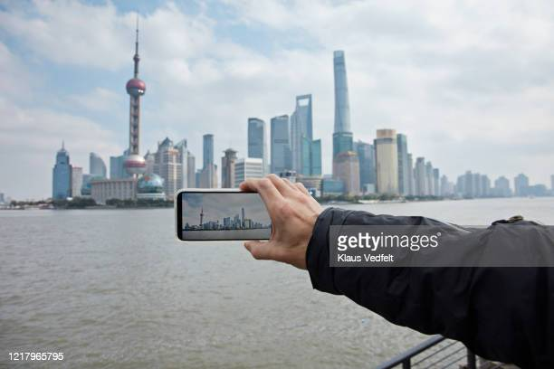 man photographing cityscape by huangpu river - quayside stock pictures, royalty-free photos & images