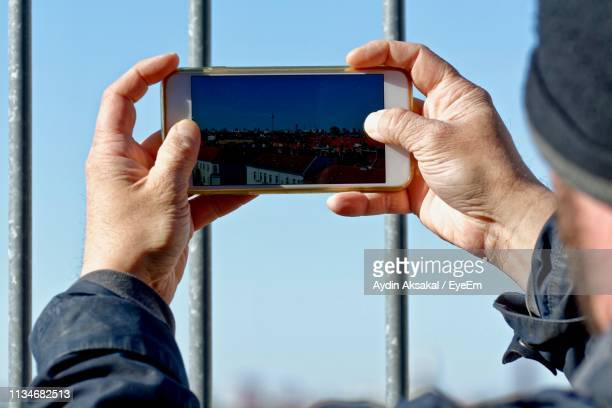 Man Photographing Cityscape From Mobile Phone