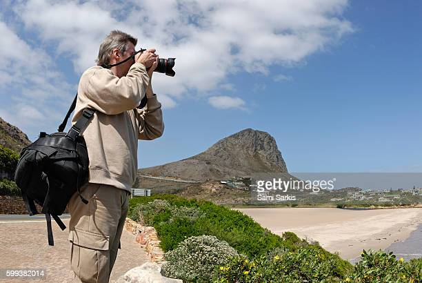 Man photographing coastal landscape between Gordon's Bay and Betty's Bay, Western Cape Province, South Africa