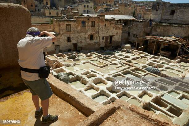 Man photographing dilapidated ancient ruins in cityscape, Medina, Fes, Morocco