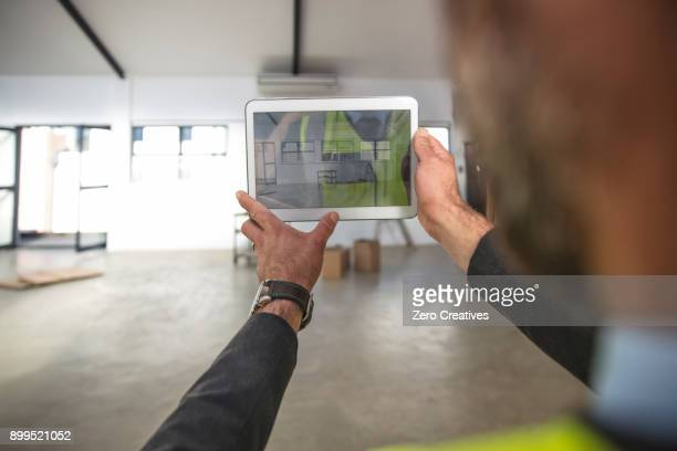 Man photographing empty office space with digital tablet