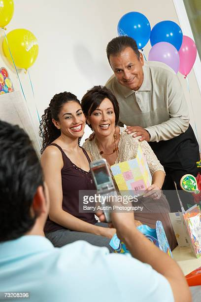 man photographing family using camera phone at birthday party - happy birthday images for sister stock pictures, royalty-free photos & images