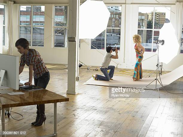 Man photographing female model in photo studio, stylist in foreground