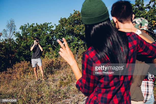 Man photographing friends in forest