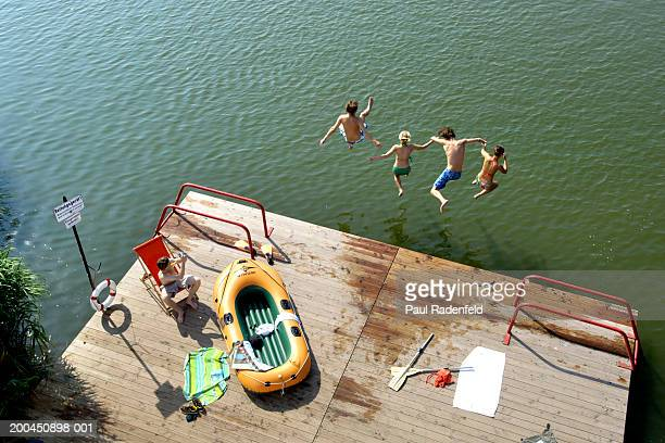 Man photographing friends jumping into lake from pier, elevated view