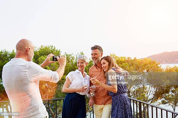 Man photographing friends though mobile phone