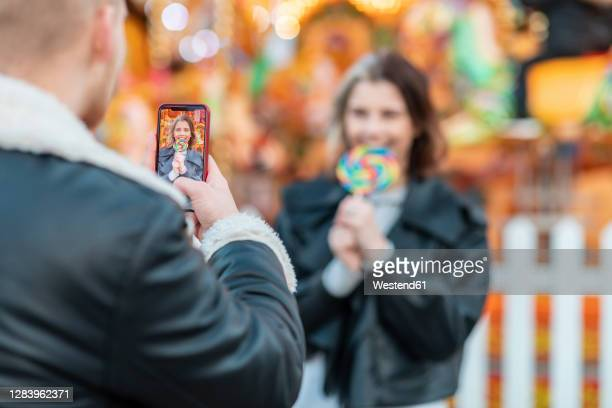 man photographing girlfriend eating lollipop with smart phone at amusement park - girlfriend stock pictures, royalty-free photos & images