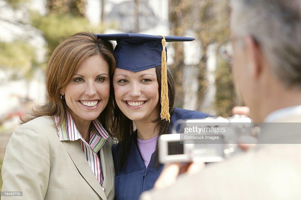 Man photographing graduate : Stockfoto