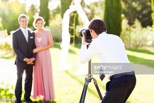 Man Photographing Groomsman And Bridesmaid At Garden Wedding