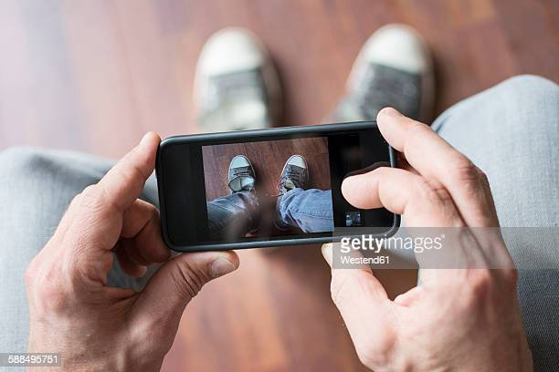 Man photographing his shoes with smartphone