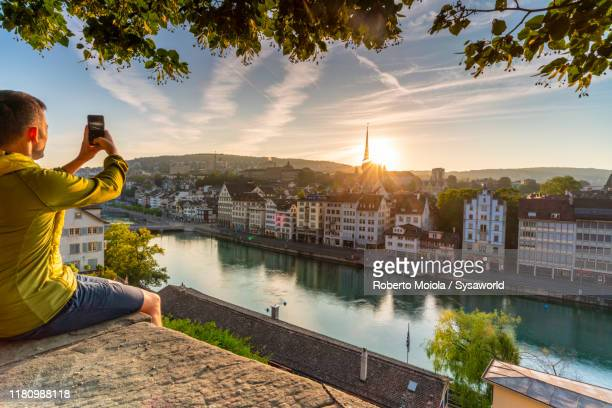 man photographing limmat river at dawn, zurich - zurich stock pictures, royalty-free photos & images