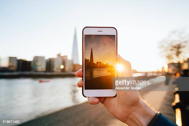 Man photographing London skyline with smartphone