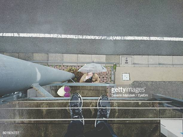 Man photographing low section of friend