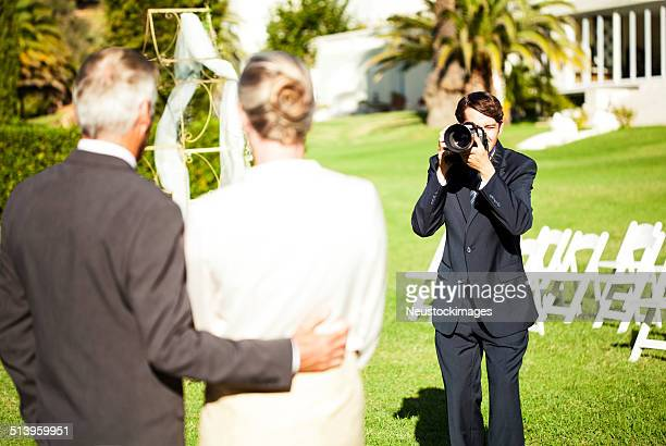 Man Photographing Mature Couple At Outdoor Wedding