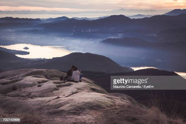 Man Photographing Mountains Against Sky