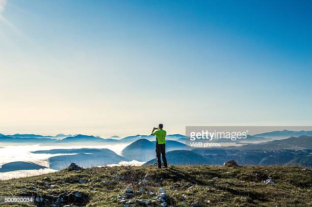 Man photographing mountains rising through Low Cloud
