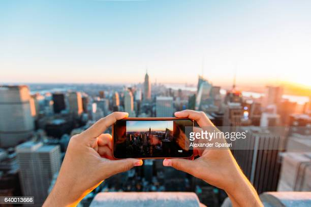 Man photographing New York skyline with smartphone
