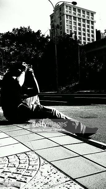 man photographing on footpath - photographic film camera stock photos and pictures