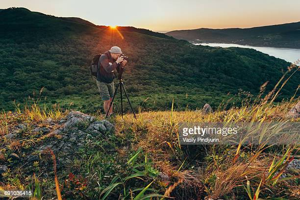 Man photographing on grassy field during sunset