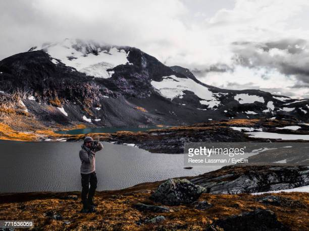 Man Photographing On Mountain During Winter