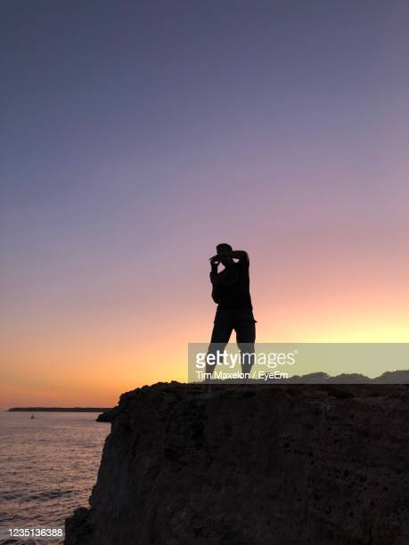 man photographing on rock at sea shore against sky during sunset - manacor stock pictures, royalty-free photos & images