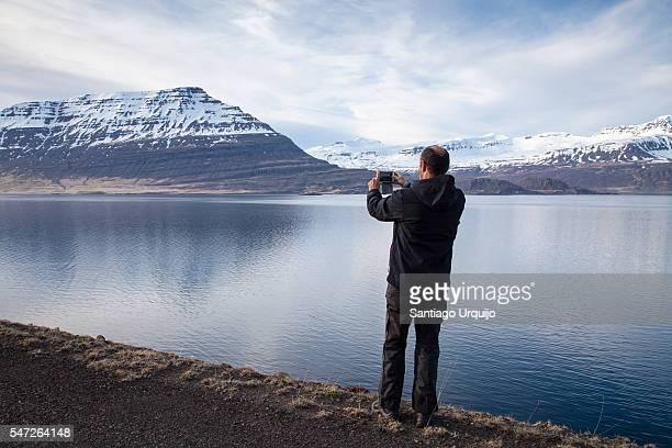 Man photographing Reydarfjordur fjord with smartphone