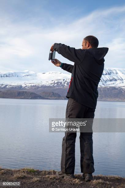 man photographing reydarfjordur fjord with smartphone - capturing an image stock pictures, royalty-free photos & images