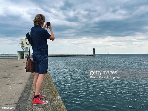 Man Photographing Sea Through Smart Phone While Standing On Walkway