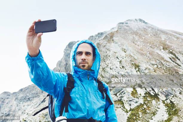 Man photographing self on smartphone in mountain