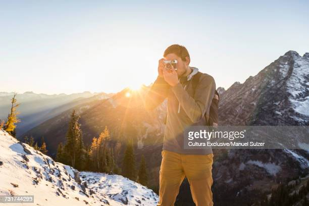 Man photographing snow covered North Cascades mountain range, Washington State, USA
