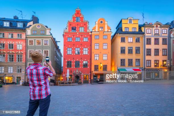 man photographing stortorget square, gamla stan, stockholm - stockholm stock pictures, royalty-free photos & images