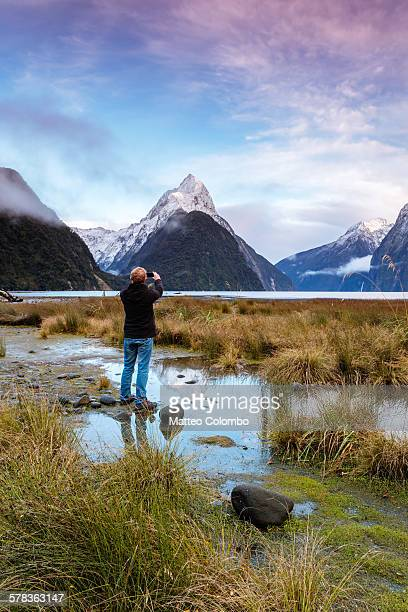 Man photographing sunrise at Milford Sound