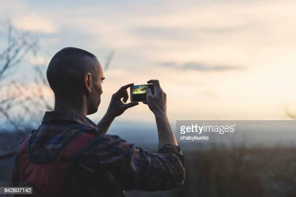 Homme de photographier le coucher de soleil dans la forêt