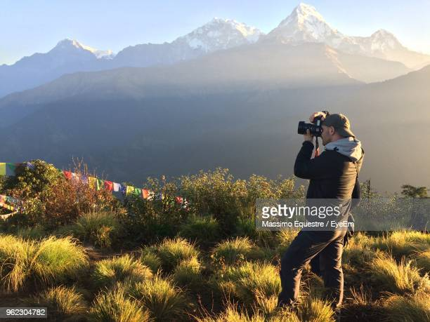 man photographing through camera while standing on mountain - photographe professionnel photos et images de collection