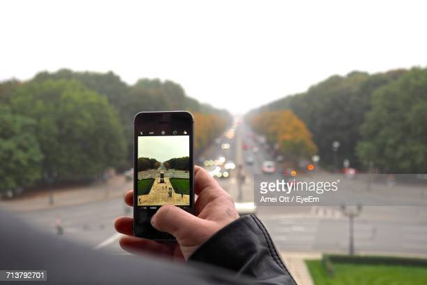 Man Photographing Using Mobile Phone On Street