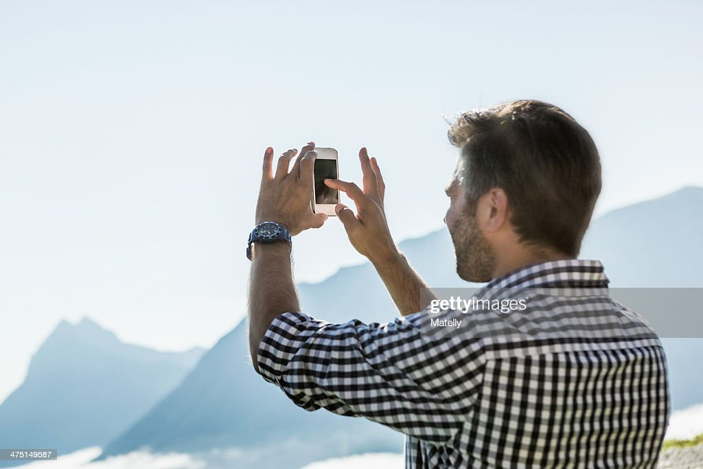 Man photographing view on his mobile phone, Tyrol, Austria : Stock Photo