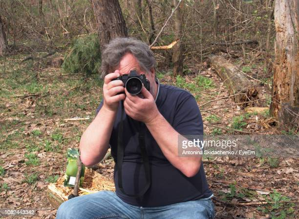 Man Photographing While Sitting On Field