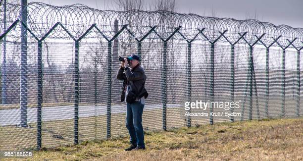 Man Photographing While Standing By Fence