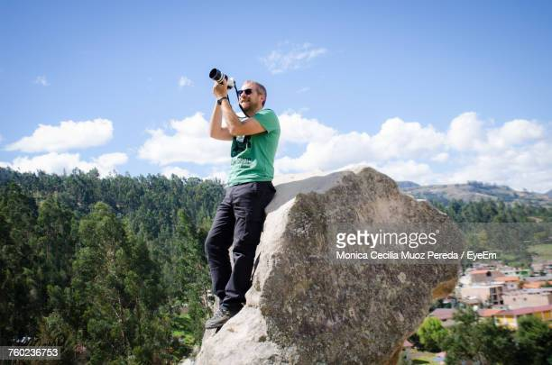 Man Photographing While Standing On Rock Against Sky