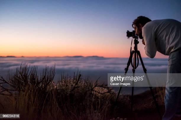 man photographing with camera against sky during sunset - pico de teide stock pictures, royalty-free photos & images