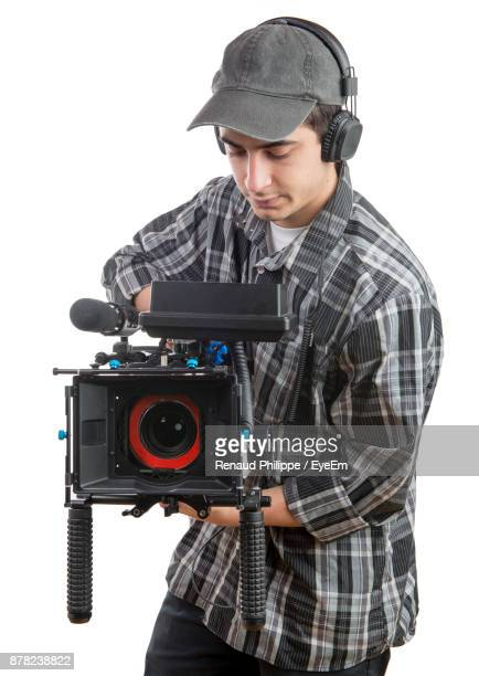 man photographing with camera against white background - cinematographer stock pictures, royalty-free photos & images