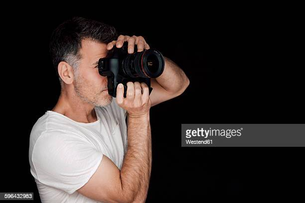 Man photographing with camera in front of black background