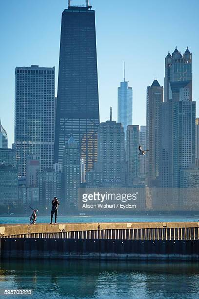 Man Photographing With Camera While Standing On Retaining Wall By Lake With City Buildings Seen In Background