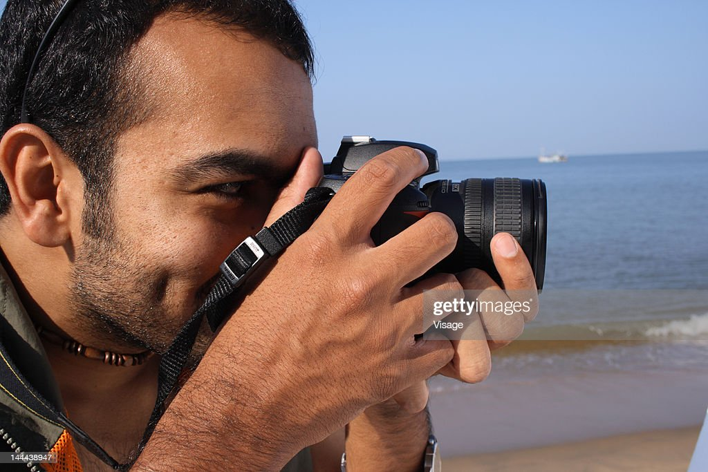 Man photographing with his SLR camera : Stock Photo