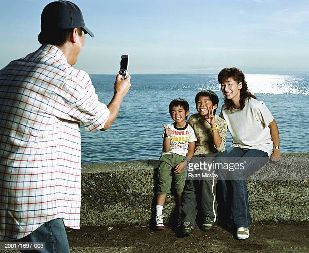 Man photographing woman and two sons (5-10) on rock wall beside sea