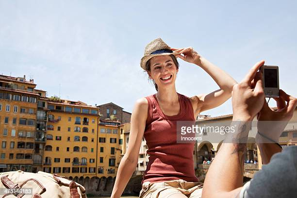 Man photographing woman on Ponte Vecchio, Florence, Tuscany, Italy