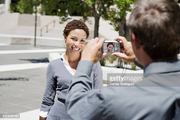 Man photographing woman with digital camera