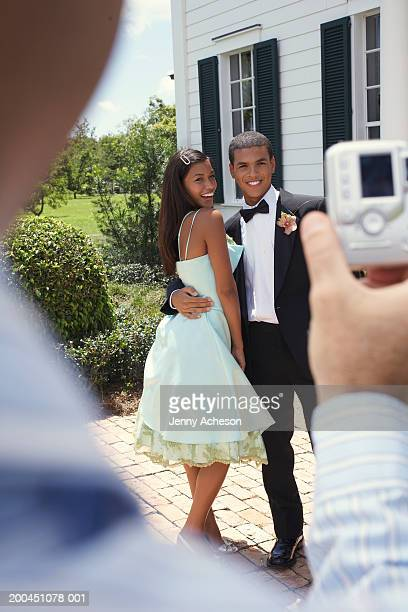 man photographing young couple wearing evening dress, outdoors,smiling - cocktail dress stock pictures, royalty-free photos & images